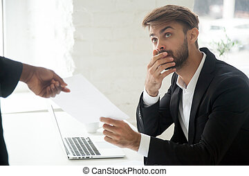 Shocked worker getting dismissal notice from black boss