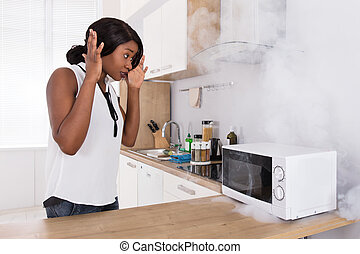 Woman Looking At Burnt Pizza In Microwave Oven