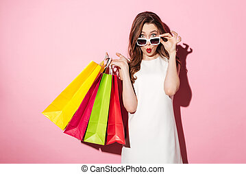 Shocked young brunette lady with shopping bags - Image of a...