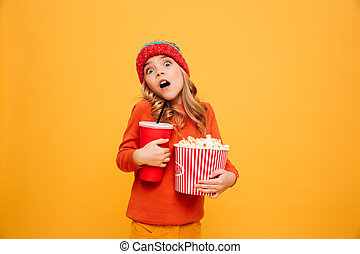 Shocked Young girl in sweater and hat holding popcorn