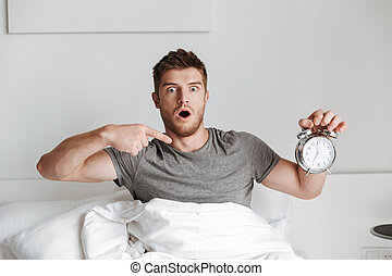 Shocked young man showing alarm clock while sitting in bed
