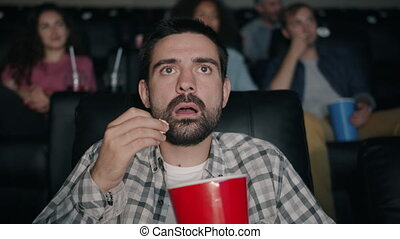 Shocked young man watching film in cinema with open mouth...