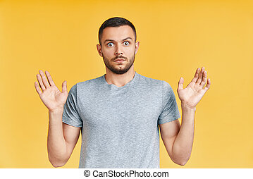Shocked young man with arms up looking amazed in camera over yellow background