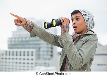 Shocked young model in winter clothes showing something in the sky outside on a cloudy day