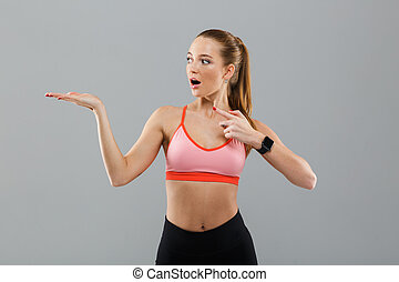 Shocked young sports woman pointing to copyspace.