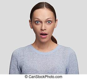 shocked young woman looking at camera