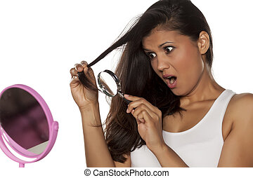 shocked young woman looks at her damaged hair