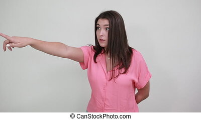 Shocked young woman pointing aside, keeping hand behind back