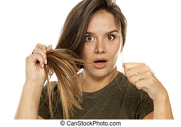 Shocked young woman showing her loss hair