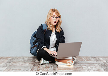 Shocked young woman student using laptop computer.
