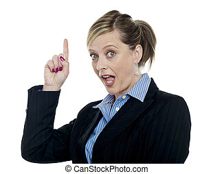 Shocking corporate woman pointing upwards on white...