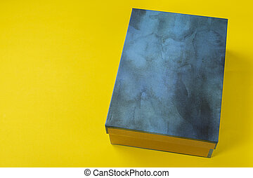 Shoe box in blue on a yellow background.