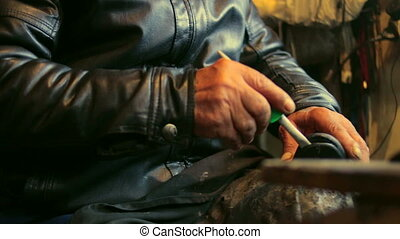 Shoe maker is repairing a shoe sticking it with glue at his...
