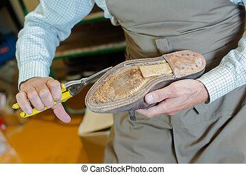Shoe maker preparing a shoe