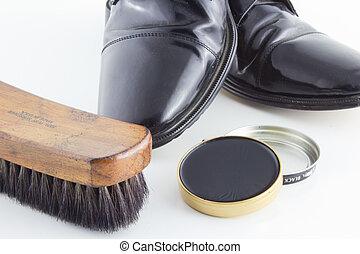 Shoe shine brush and polish on white background.