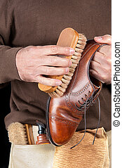 Shoe shiner - A shoe shiner works on the final buffing of a...