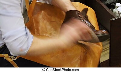 Shoe shiner polishes the boots of brown leather with a special brush