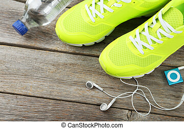 Shoe, water and headphones on grey wooden background