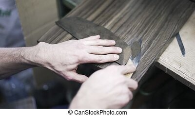 Shoemaker cutting leather with a knife