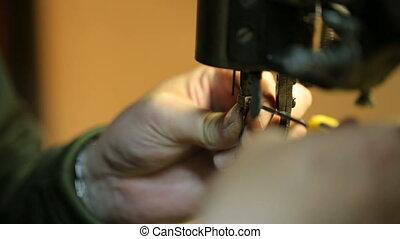 Shoemaker preparing sewing-machine. Close shot.
