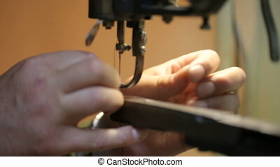 Shoemaker preparing sewing-machine. Close shot.