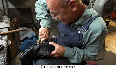 Shoemaker repairing a shoe in workshop 4k cut the taps on the shoes