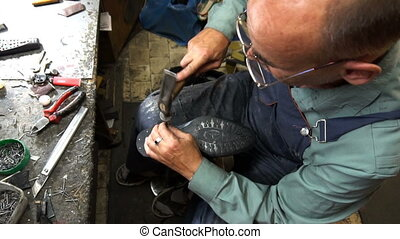 Shoemaker repairing a shoe in workshop 4k nail the heel cap to the heel
