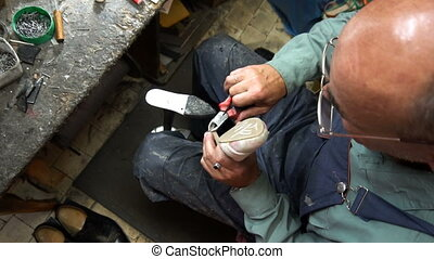 Shoemaker repairing a shoe in workshop 4k