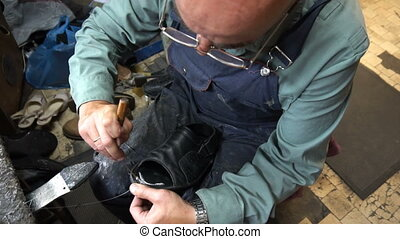 Shoemaker repairing a shoe in workshop 4k,sizing shoes