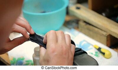 Shoemaker repairing female shoe. Close shot.
