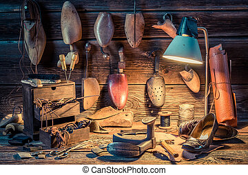 Shoemaker workshop with tools, shoes and laces