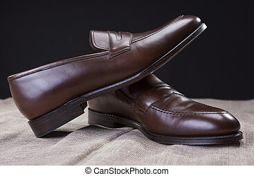 Shoes Concepts and Ideas. Closeup of Stylish Modern Brown Leather Penny Loafer Shoes Against Black Background