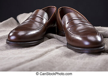 Shoes Concepts and Ideas. Closeup of Stylish Modern Brown Leather Penny Loafer Shoes Against Black Background.