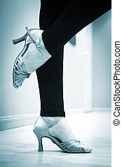 Dancing shoes feet and legs of female ballroom and latin salsa dancer dance teacher in dance school rehearsal room class.