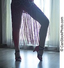 Dancing shoes feet and long slim legs of female ballroom and latin salsa dancer dance teacher in dance school rehearsal room class.