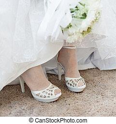 Shoes of bride under wedding dress