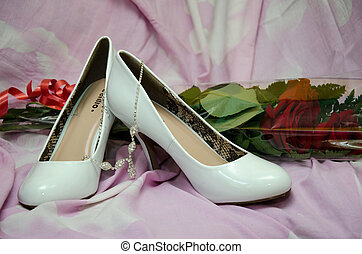 Shoes of the bride against flowers