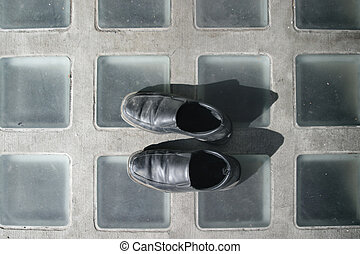 shoes on pavement - a pair of dirty black mens shoes on ...