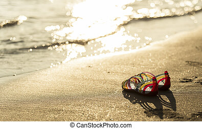 Shoes on the beach in sunset time