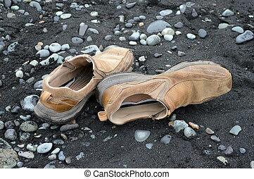 Shoes on the beach - A pair of brown shoes on a black sand...