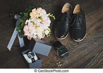 Shoes, rings and a bouquet with a clock on the table 666. - ...
