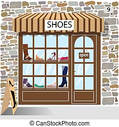 Shoes shop building facade of stone. Shoes and boots in the ...