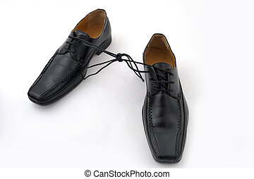 Pair of black man shoes tied together on white background