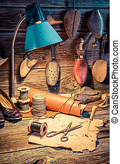Shoes, tools and leather in old cobbler workshop