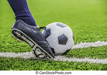 soccer ball with his feet on the football field