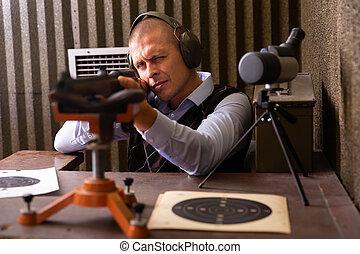Portrait of focused shooter practicing shotgun shooting in sitting position at firing range