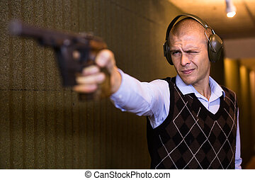 Concentrated shooter wearing protective earmuffs practicing sport handgun shooting at firing range