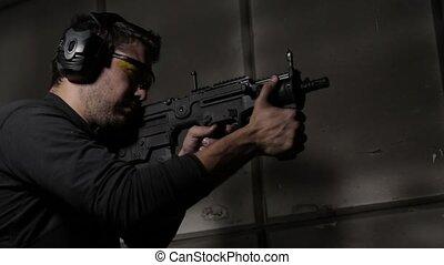 Shooting a rifle low angle view - Man shooting a rifle side...