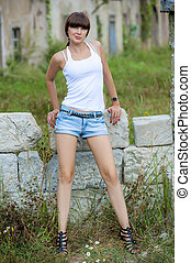 Shooting brunette on a background of ruined stone wall