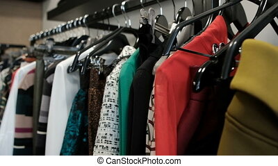 Shooting clothes in store, long line with black hangers with dresses